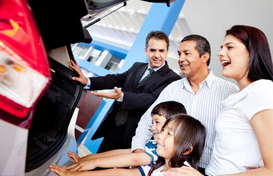 Salesperson with a family at a car dealership looking at a car