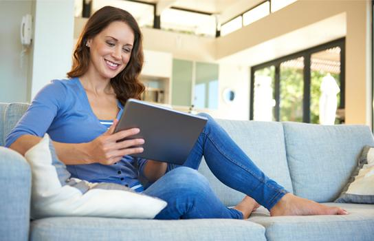 Woman looking at iPad on couch